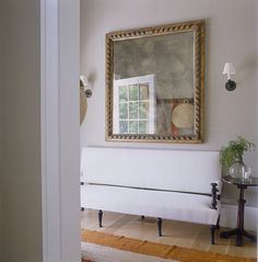 In the entry, a 19th-century muslin-covered settee from Bloom is just right for donning summer flip-flops or shucking winter Wellies. A 17th-century Venetian mirror hangs on a wall painted Farrow & Ball's Light Gray.   - HouseBeautiful.com