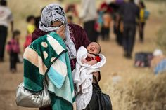 "A young mother crosses the border from Syria and becomes a refugee. In her arms she carries her one month old son Hamid. ""Since he was born there has been non stop bombing everyday"" UNHCR / S. Rich / April 2013"