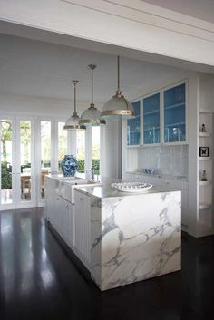 Dark flooring, a marble waterfall island, classic lighting fixtures, and the surprise of vividly blue painted upper cabinet interiors- tradition made fun!  Interior design by Burley Katon Halliday.