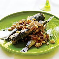 Pan-Fried Sardines with Sweet-and-Sour Onions, Pine Nuts, and Raisins | MyRecipes.com.  Based on a classic Sicilian marinated fried version, this is a great entry-level way to try sardines. The vinegar adds a mouthwatering acidity that balances the oiliness of the fish—and also, in pre-refrigeration days, helped preserve it.