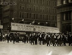 "Demonstrators carry a large banner through the streets of New York, New York, during a 4th of July anti-Prohibition parade. The banner reads ""WE HOLD THE 18th AMENDMENT TO BE UNCONSTITUTIONAL."""