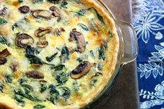 A cheesy quiche with spinach and mushrooms