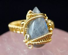 A delicate, unique, handmade, wire wrapped ring with Labradorite .  Ring was designed and made by Me, using an extremely labor-intensive and precise wire-wrapping technique, with 24 K gold plated wire. On a buyers request size can be adjusted by plus 1 or minus 1.  Dimensions: Jewelry Size: 13 EUR ( 6.5 USA ) Inner diameter: 16,6 mm Width of ring: 3 mm  To create this ring I used 24 K gold plated copper wire produced by a German company GRIFFIN, a leading supplier of craft wires for…