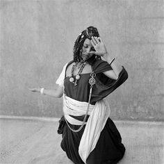 - Besancenot Jean (1902-1992) Attitude de la danseuse Aït Oussa pendant la Guedra. Elle est vêtue d'un drapé double de khount bleu à même la peau. La ceinture retenant le drapé a été dénouée, dévoilant la poitrine. - Arago
