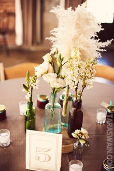 centerpiece....like the idea of the log piece with old bottles, flowers