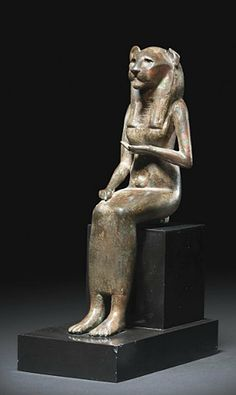 AN EGYPTIAN BRONZE SEKHMET LATE PERIOD, DYNASTY XXVI, CIRCA 664-525 B.C. The lion-headed goddess seated, wearing a close-fitting ankle-length garment, her left hand held to her breast, her right arm resting on her thigh, wearing a striated tripartite wig and collar 6¾ in. (17.2 cm.) high