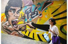 A woman walks past a graffiti portrait of Bruce Lee painted on a wall outside a gallery to mark the 40th anniversary of the death of the kung fu star, in Hong Kong on Tuesday July 16, 2013. Lee died on July 20, 1973 and a memorial exhibition will be held at Hong Kong's Heritage Museum.