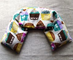 Flaxseed Heat Pack with Organic Herbs - Cupcake print - My microwavable herbal flax seed pillows are made with Certified Organic flaxseed.  This wrap is made with cotton cupcake decor fabric.  The neck wrap can be used in the microwave for heat therapy, or store in the freezer for cold therapy.   They are great for relaxing after a long hard day.  When heated in the microwave they give off sustained moist heat. This pillow is approximately 22 inches long by 5 inches wide and contain…