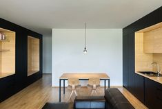 Units extending along the walls of this apartment are interrupted by a oak inserts including high bookshelves, as well as a surface that can be used as a desk.