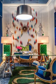 Crazy colorfulness: High ceiling, chairs, sculpture + glass top table, art, and chandelier.