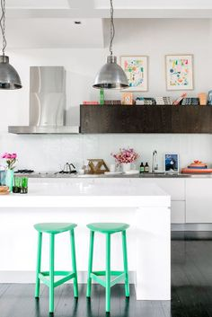 We just can't get enough of mint green in a kitchen space, and this kitchen design incorporates that gorgeous colour perfectly. We love the subtle colour splashes against the minimalistic flooring and surfaces - and any room which is filled with books is a winner for us.