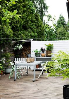 Botanical wooden terrace with a smart outdoor table on wheels and a lot of green plants.