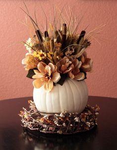 Blumenarrangement in einer weißen Vase auf Herbstkranz