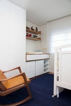 """Para o quarto do bebê, no apartamento em Perdizes, zona oeste de São Paulo, as arquitetas Débora Stefanelli e Pérola Machado desenvolveram alguns móveis sob medida, na cor branca. Para """"aquecer"""" o ambiente, foram empregados o o tapete em tom azul escuro e a poltrona de madeira (Dpot)"""