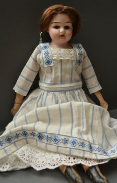 """One of the less common """"named"""" dolls made by Armand Marseille. Just under 40cm (16"""") tall, she has a perfect bisque shoulderhead with fixed brown glass eyes, four tiny teeth in her open mouth and an antique and rather fragile chestnut-brown mohair wig tied with an antique pale blue silk ribbon. She is marked """"Alma"""" and """"13/0."""" on the back of her neck. Her body is made of pink cloth, with beige cloth hands and sewn-on black oilcloth boots. It is stamped """"Hair-Stuffed - Made in Germany"""" on…"""