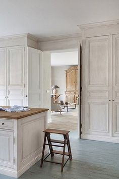 Classic white kitchen with painted floors, floor to ceiling cupboards and, wood tops.
