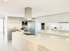 Here's a stark white contemporary kitchen design with super long island and a minimalist vibe. White Contemporary Kitchen, Contemporary Kitchen Cabinets, Kitchen Cabinets Decor, Kitchen Cabinet Design, Kitchen Layout, Cabinet Decor, Kitchen Ideas, Blue Cabinets, Modern Kitchens