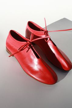 """Half boot, half dress shoe, these booties do it all. The stunning red color and simple bow closure are eye-catching and are sure to take any outfit to the next level. * Round toe * Keyhole closure with leather lace-up tie * Low-cut bootie style * 1/2"""" stacked leather he"""