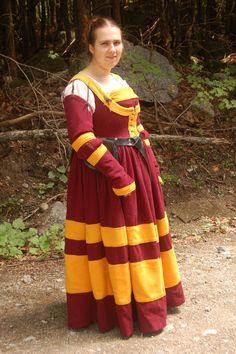 Ondanks haar rijke kleding, hoeft deze Quenellaanse dame niet gelijk van adel te zijn. Men is daar nou eenmaal rijk genoeg om, zelfs voor de simpele burgerij, zulke kleding te veroorloven.