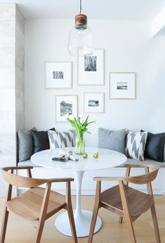 A wood and glass light pendant hangs over a Saarinen Dining Table seating two mid-century modern dining chairs and a white built in dining bench topped with a gray seat cushion and gray and white pillows positioned under a photo wall.