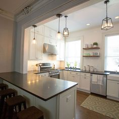 This u-shaped traditional kitchen features peninsula seating, open shelving and perfectly painted white Shaker cabinets in the CliqStudios Dayton style. The simple crown molding in the kitchen complements, without competing against, the traditional stacked crown molding in the adjacent room.