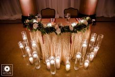 Choose a sweetheart head table like this decorated in gold sequin linen with floating votive candles and floral design for your perfect wedding reception