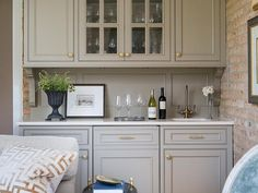 Amazing living room features a wet bar boasting gray cabinets adorned with brass hardware topped with natural stone fitted with a square sink and gold gooseneck faucet under glass cabinets filled with wine glasses.