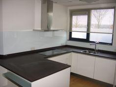 Achterwand in keuken van gelakt wit glas.
