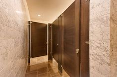 Ironwood Manufacturing wood veneer toilet partition and bathroom door with opposing wood grain direction combination. Beautiful, upscale public restroom stalls.