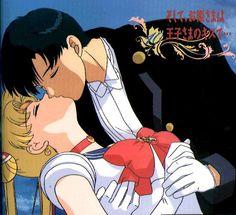 Sailor Moon and Tuxedo Mask share a kiss.