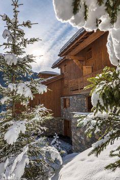 Chalet bois et pierre sous la neige, en montagne, entouré de sapins.