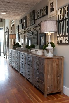 Love this! Two adjacent long reclaimed wood cabinets with array of graphic artwork on wall above.