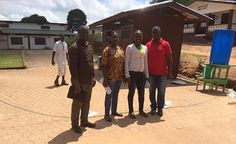 Outside CB Dunbar Maternity Hospital in Bong County, during the Ebola outbreak.  Standing just outside a cordon protecting visitors from entering the hospital until they have washed their hands in chlorinated water and had their temperatures taken are from left to right Jeremiah Akoi (MCAI logistician), Naomi Lewis then Hannah Gibson (obstetric clinicians in training).  On the right is Dr Obed Dolo consultant obstetrician and the Director of the Hospital.  Dr Dolo, with support from MCAI's…