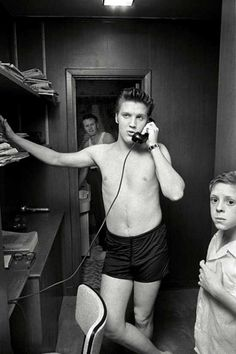 Elvis Presley on the phone at his parents' house with his cousin Billy Smith.