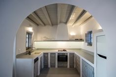 Paros, Greece. Traditional built hood, cupboards, counter covered by cement mortar and wooden beams on the ceiling.