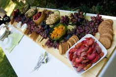a backyard wedding: cheese, crackers, grapes, nuts and olives spread. Alot of people suggested for inexpensive appetizers to go to costco and get various snacks, like crackers  cheese, or a few bowls of various nuts. Things to snack on, not too heavy and not too much.