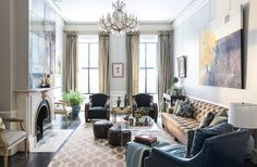 """The living room, with a pair of French Art Deco chairs and a long tufted sofa, is the""""catchall room"""" and the site offamily time and game-day hosting (there's a TV cleverly hidden behind the antique mirror above the mantel).""""I wanted it to feel elegant enough to hold its own in this old beautiful brownstone but then be family-friendly and approachable enough,"""" Nina says."""