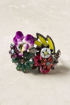 """Candied Violets Cuff  style # 25550153  Fashioned from bits of vintage fabric and glimmering Swarovski crystals, expertly-shaped petals give this handcrafted cuff a toothsome sparkle. Handmade by Elizabeth Cole.   Hinge closure   Swarovski crystal, brass, hematite plated brass, vintage fabric   5.5""""L, 2.5""""W   Handmade in USA  $98.00"""