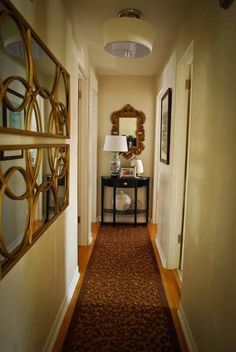 decorative mirrors - great for long narrow hallways.  also, something at the end, even if mine is a door, i can put up some light artwork or a mirror to draw the eye.