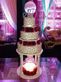 This wedding cake featured a fountain, dark red roses, gold ribbon and a vine design. #wedding #weddingcakes