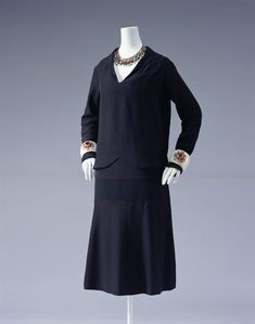 Dress c.1927  Designer:   Gabrielle Chanel  Brand:   Chanel  Label:   CHANEL  Material:   Black silk satin-back crepe; low waist, straight silhouette; creative use of different textures of fabric; ribbon decoration.