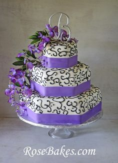 Wisteria Purple & Black Wedding Cake.  This is a 3 tiered hexagon shaped cake with purple ribbon borders, black scrolling (scroll work) and wisteria cascading down the sides!   Click over for more pics and details at RoseBakes.com