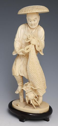 """JAPANESE CARVED IVORY OKIMONO FISHERMAN W DRAGON Japanese carved ivory okimono, late 19th/early 20th C., depicting a startled fisherman with a captured dragon coming out of his net. Highly detailed with monochrome staining to enhance details. Includes base. Provenance: Private Minnesota estate. Weight: 283g without base Size: 6.75"""" without base"""