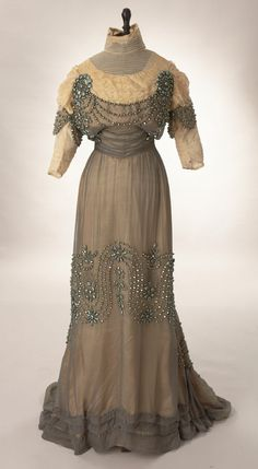 """1912: """"grey silk chiffon over ivory China silk ... upper bodice and sleeves are ivory lace over cream silk. ... Satin covered discs accented the neckline between chiffon and tulle. They are also used at the sleeve hem. ... The skirt is gently gathered into the waistline seam. Decorating the reception gown are these amazing iridescent metal shells all hand painted and hand stitched in place. There are various sizes throughout the gown. They are made to look like fresh water pearls."""" Ebay"""