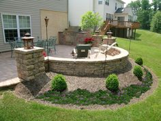 A custom patio from a walk out finished basement with a built in grill, pillars and a sitting wall for additional seating extends the living space of this house to the outdoors.