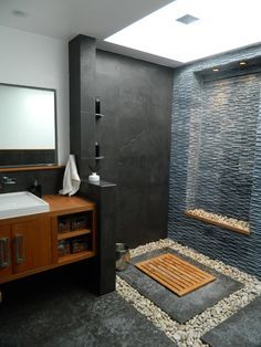 Balinese modern bathroom _ Gerson Residence by Susan Thiel Coon. => 8 feet skylight => river rock => hidden shower drain => limestone / teak finishes