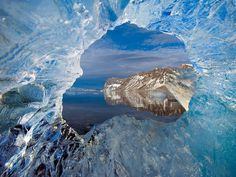 Photograph by Paul Nicklen, National Geographic    The Hornsund fjord is viewed through glacier ice in Svalbard, Norway's Arctic archipelago.