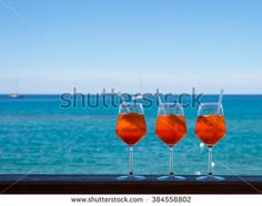 Refreshing aperitif Aperol spritz on a background of blue sea and boats