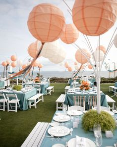 Wedding reception decorations - coral lanterns and sea green tables. Photo by Aaron Delesie via Mindy Rice Event Design.