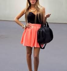 low cut black shirt with a black handbag orange skirt